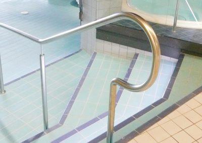 Trappa med ledstång ner i en pool i kokpunkten simhall